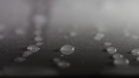 Texture of water on a smooth dark surface. Isolated drops of rain. Beads of water, wet steam condensation. Pattern of refreshing water moisture. Sliding rain drops on a window.