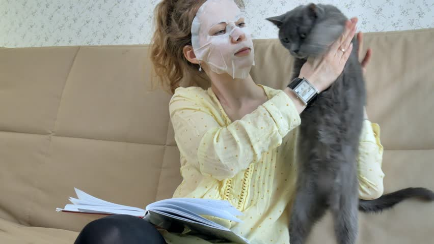 Young woman doing facial mask mask with cleansing mask on face in kitchen at home cat 4k