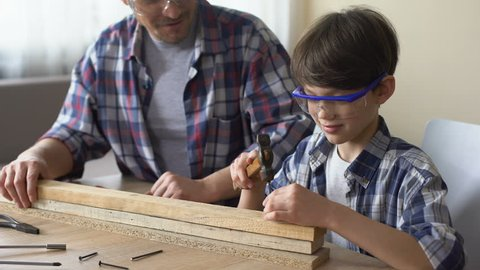 Attentive little boy hammering nail in wooden plank, father supporting his kid