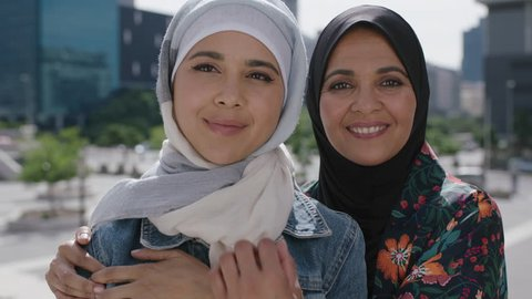 close up portrait of muslim mother and daughter smiling cheerful embrace posing taking selfie photo using smartphone in sunny urban city wearing hijab headscarf