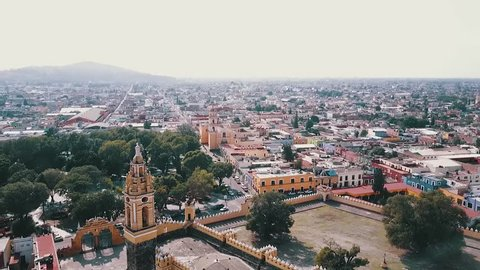 Aerial footage of cathedral and city center in Cholula, Puebla. You can see the colors and colonial buildings around the center.