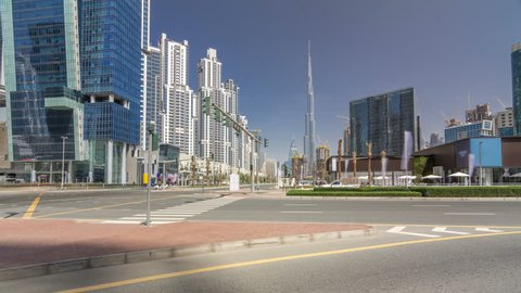 Panoramic timelapse hyperlapse view of business bay and downtown area of Dubai. Modern skyscrapers and blue sky. View from intersection with traffic on the road