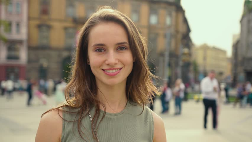 Portrait young attractive smile woman look at camera at city center feel happy fashion girl summer face technology sun beautiful slow motion street | Shutterstock HD Video #1010483687