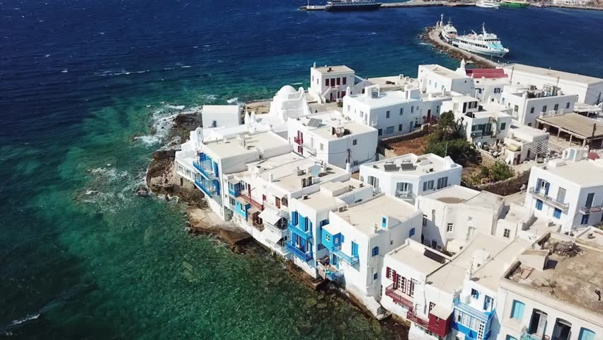 Aerial drone bird's eye view video of iconic little Venice and church of Paraportiani in chora of Mykonos island, Cyclades, Greece