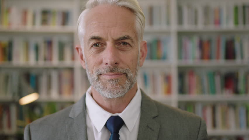 Portrait of professional businessman in library adjusting his tie gentleman architect professor lecturer | Shutterstock HD Video #1010501327