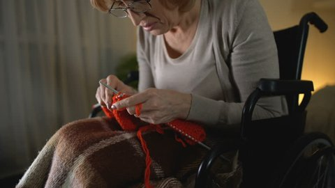 Old knitting woman feeling desperate of shaking hands illness, hopelessness