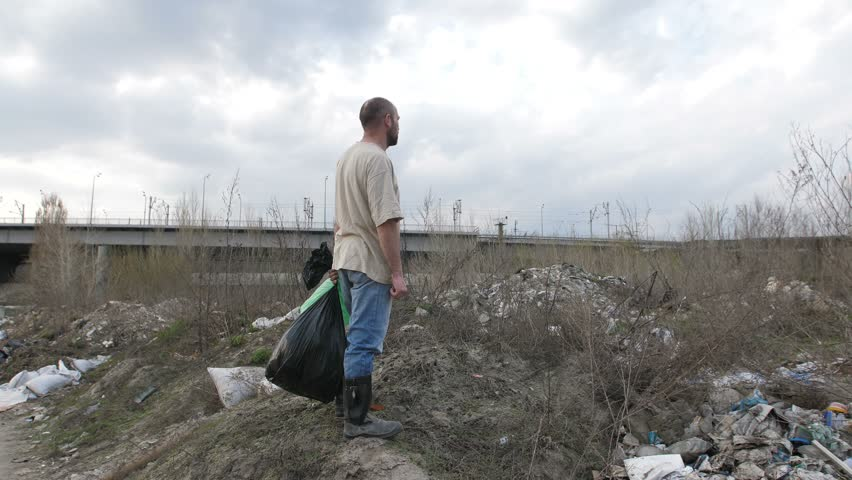 Back view of mature homeless man in dirty t-shirt standing on the hill at garbage dump with bin bags in hand. Camera rotating 180 degrees. Environmental problems and pollution concept.