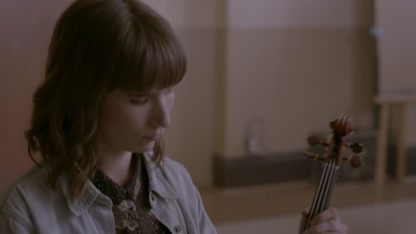 Female musician tuning her violin HD stock video. Alexa camera