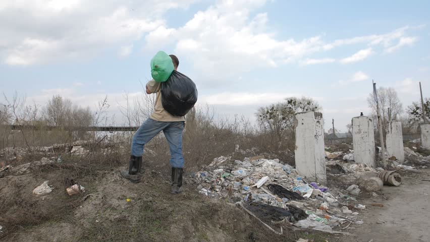Homeless man with trash bin bags on his shoulder standing on the hill at garbage dump site in city. Slow motion, camera rotating 180 degrees. Environmental problems and pollution concept.