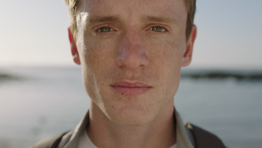 Close up portrait of handsome young man looking thoughtful pensive on seaside background focused confident