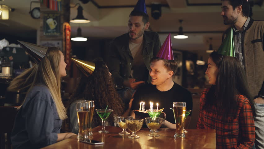 Best friends are congratulating young man on birthday, he is blowing out candles on cake and thanking his mates for great party. Funny holiday with friends concept.