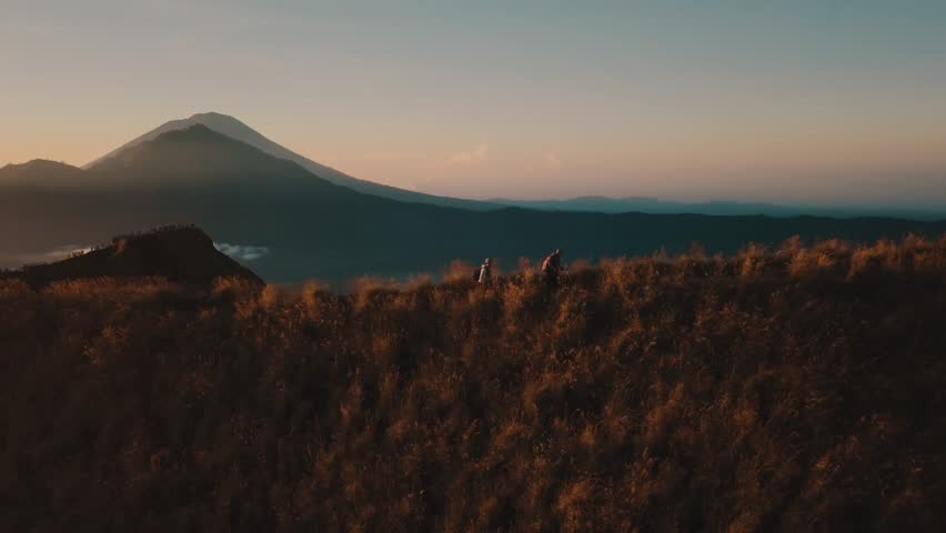 Hiking Mountain, Aerial Drone Footage Hiking Couple Hikers with Backpack Mount Batur Volcano Bali During Sunrise, View of Gunung Agung Volcano, Sun Shines Through, Beautiful Nature Landscape Indonesia