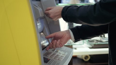 Man using his credit card in an atm for cash withdrawal, pin code money shopping mall