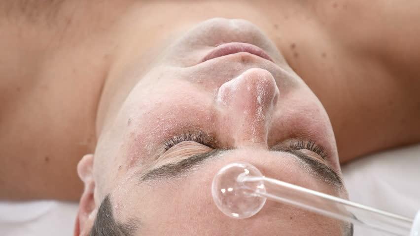 Darsonvalization. Man having darsonval therapy. Facial skin care in beauty saloon. electric darsonval massage procedure   Shutterstock HD Video #1010570747