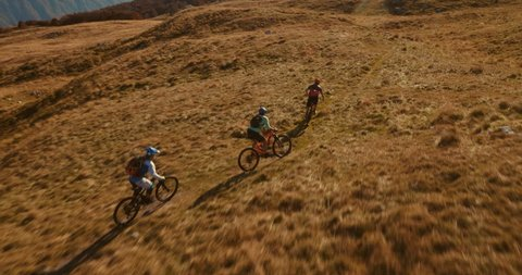 Aerial tracking shot of three mountain bikers cross-country riding to the top of the mountain with amazing peaks in the background.