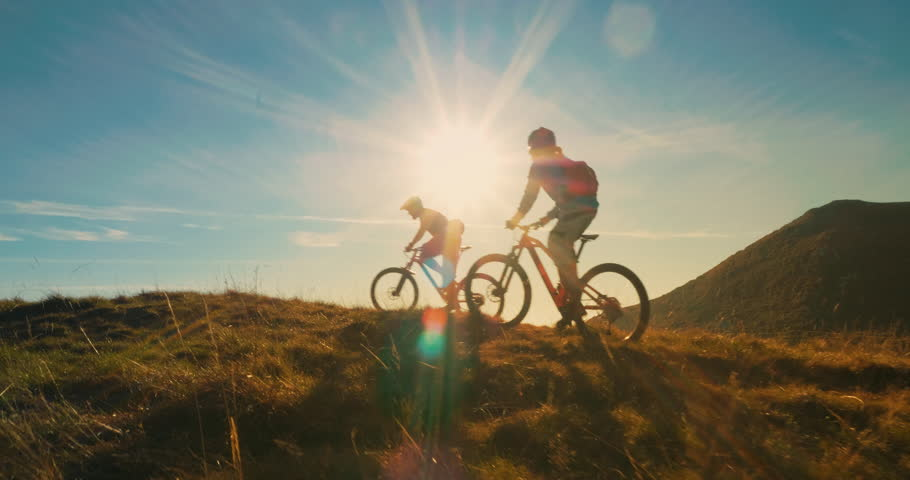Two mountain bikers riding their bikes to the top in amazing sunlight. #1010578247