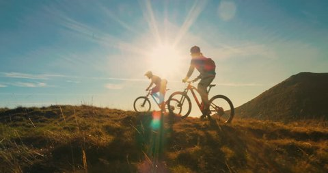 Two mountain bikers riding their bikes to the top in amazing sunlight.
