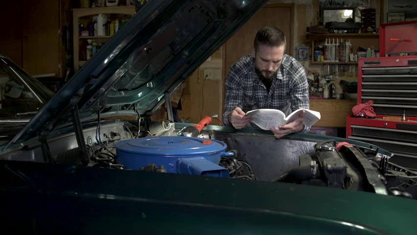 Mature man referring to car instruction manual by open car bonnet.