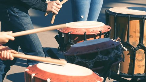 The hands of street musicians play the drums. Slow motion
