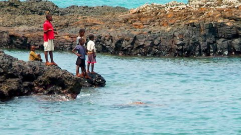 Sao Tome, Sao Tome and Principe - 08 14 2014: African children playing on rocks along the ocean coast