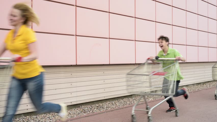 Happy family with shopping carts in a parking lot near a supermarket. People runing and engaged in purchases in shopping centre. Mom, Dad, Children having fun outdoors with shopping trolleys race.