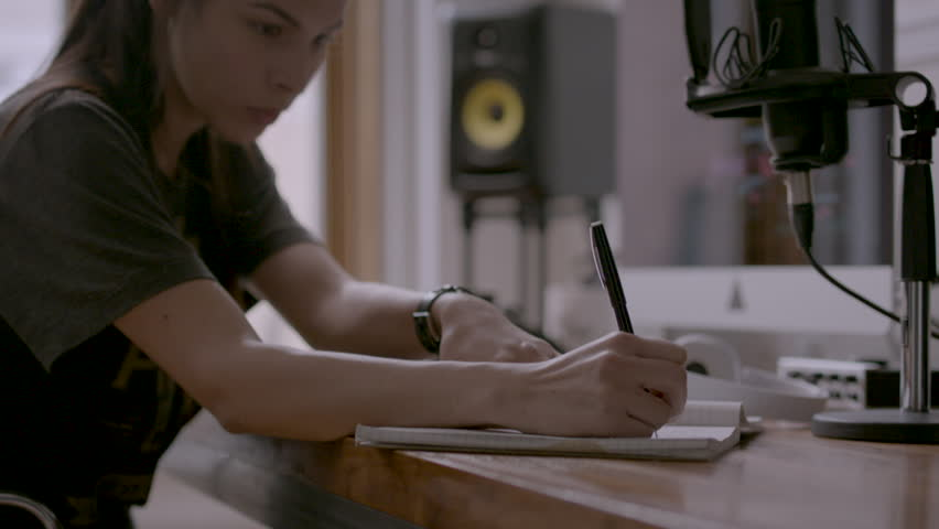 Female takes of headphones and writes in notebook HD stock video. Alexa camera