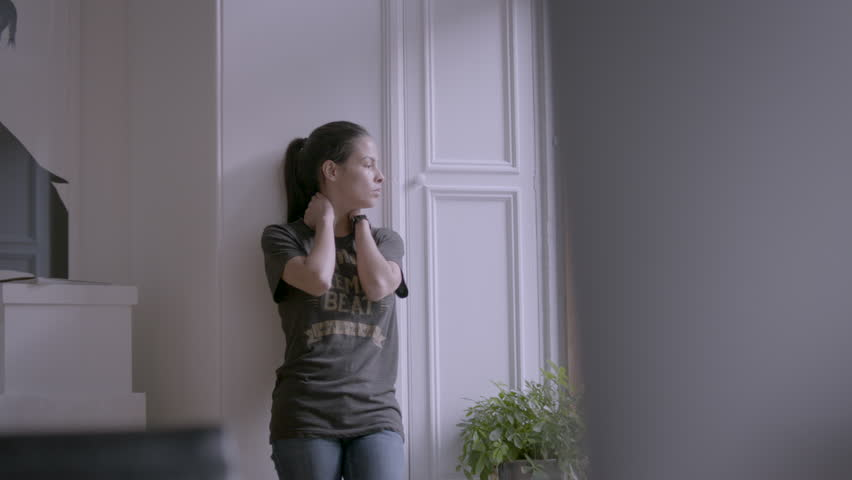 Female walks to window and looks outside while rubbing her neck HD stock video. Alexa camera | Shutterstock HD Video #1010618177