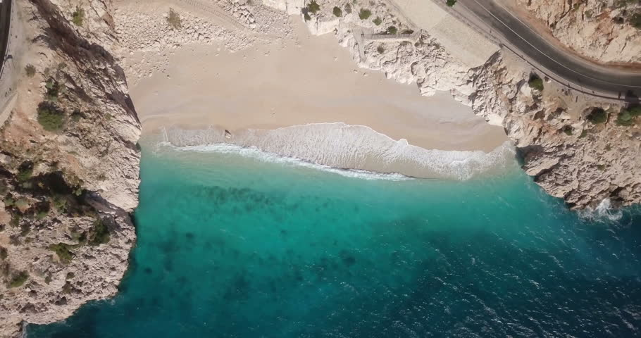 Rising, twisting aerial drone video bird's eye view directly overhead of turquoise Mediterranean water, waves breaking on Kaputas Beach near Kas, Turkey. 4k at 23.97fps