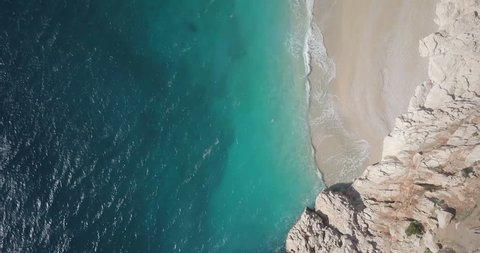 Forward aerial drone video top down bird's eye view along shoreline of Kaputas Beach and waves breaking on Turquoise Coast near Kas, Turkey. 4k at 23.97fps