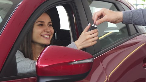 Young happy woman receiving car keys to her new automobile