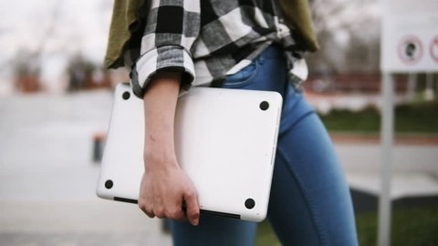Close up of an elegant girl in jeans walks through the park with a laptop in her hand. Confident walk. Side view. No face