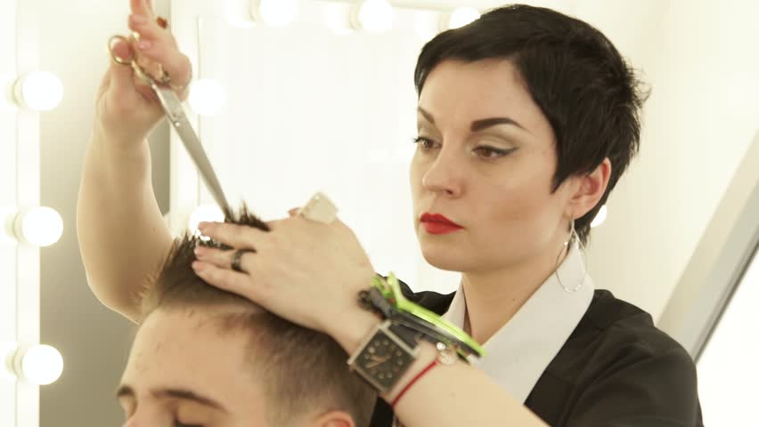Hairdresser cutting hair with professional scissors and comb in hairdressing salon. Close up haircutter making male haircut with scissors in hairdressing school