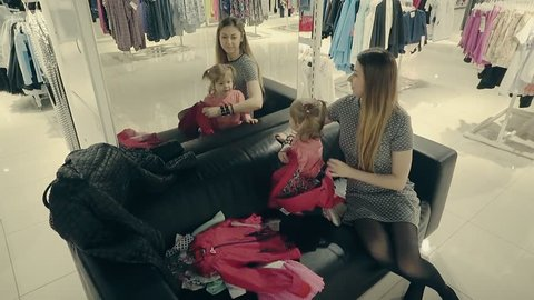 8efb664d0f A young beautiful mother with a cute baby (girl) in the store trying on