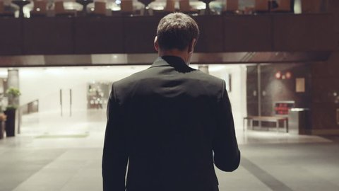 Rear view of a young businessman wearing a dark suit. Stock. Rear view of the businessman entering the hotel