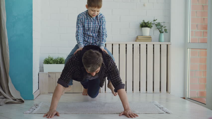 Strong active man is doing push-ups with his laughing little son sitting on his back. Sport, spending time with family, happy childhood concept.