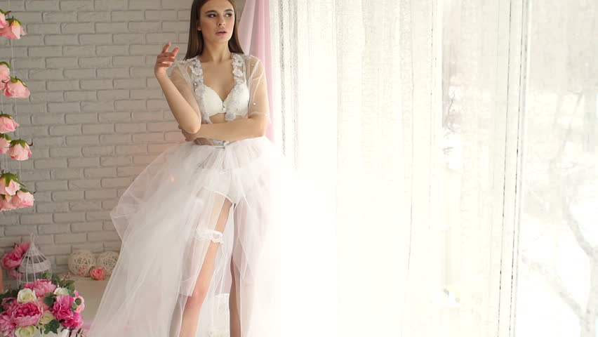 Luxurious leggy girl in lingerie and transparent negligee with a long skirt stands among the flowers near the big window.