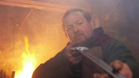The medieval blacksmith taken sword to examine metal of sword