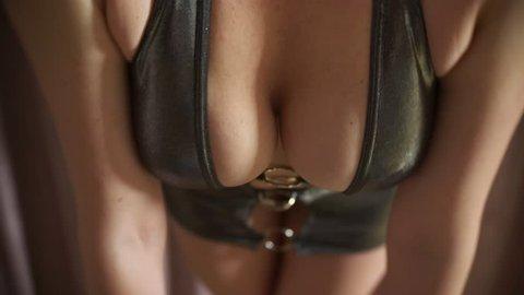 a hot seductive model in a mini-dress dancing an erotic private dance. slim body and big tits. 4k
