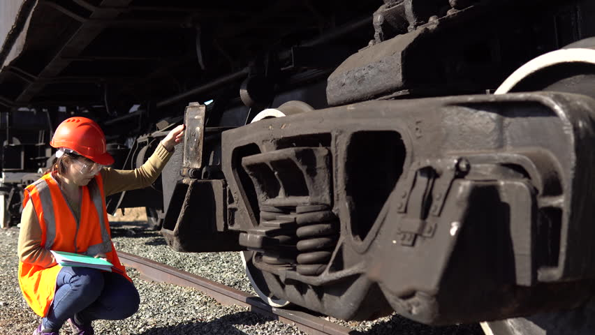 A young brunette woman railway worker in an orange vest checks the hitch unit of the freight wagon, raises the lid of the axle-box with a plain bearing and compares it with the scheme.