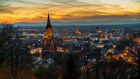 Freiburg, Germany - March 29, 2018: Freiburg Timelapse view showing city skyline including historical church at twilight transitioning from day to night