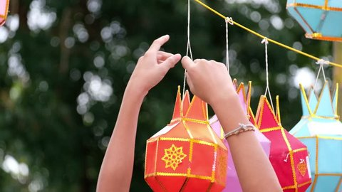 Asian People hanging the Lanna lantern on the rope to wish a desire or hope for good thing to happen, in northern thai style lanterns at Loi Krathong (Yi Peng) Festival, Chiang Mai, Thailand