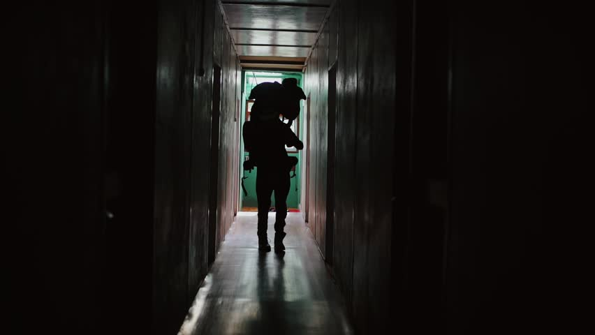 Silhouette of a tourist dancing in the hallway of the hotel. Happy traveler with a large backpack moving his hands in the dark. Slow-motion.   Shutterstock HD Video #1010902727