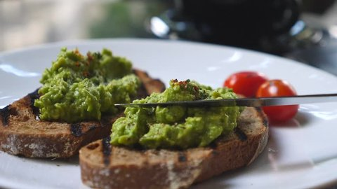 Spreading Mashed Avocado On Toast. Healthy Vegan Breakfast.