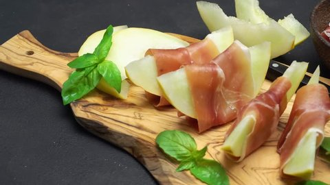 sliced prosciutto and melon on a wooden board