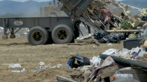 Large dump truck emptying a dumpster filled with construction waste at a landfill