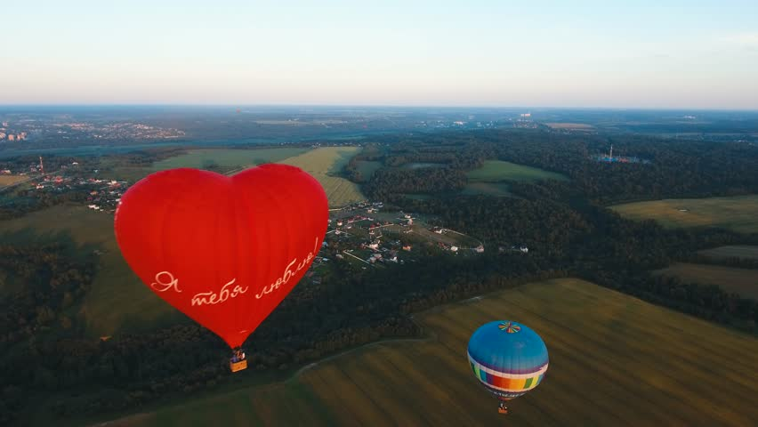 Aerial view Hot air balloon shape of a heart in the sky over a field in the countryside, beautiful sky and sunset. Aerostat fly in the countryside.Aerial footage, 4K