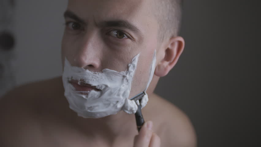 Man shaving with foam and manual razer. Close up of man shaving beard. | Shutterstock HD Video #1011001517