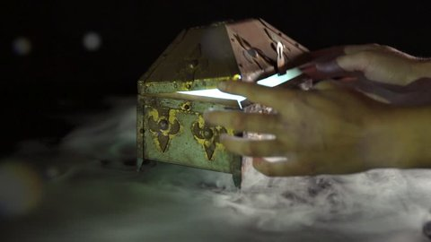 4K anonymous hands opening mysterious treasure chest / pandoras box with glowing mist / fog / smoke inside on black background