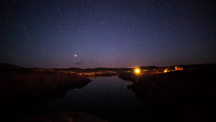 Time lapse of stars over campsites by water at Lake Powell as airplanes move through the sky.