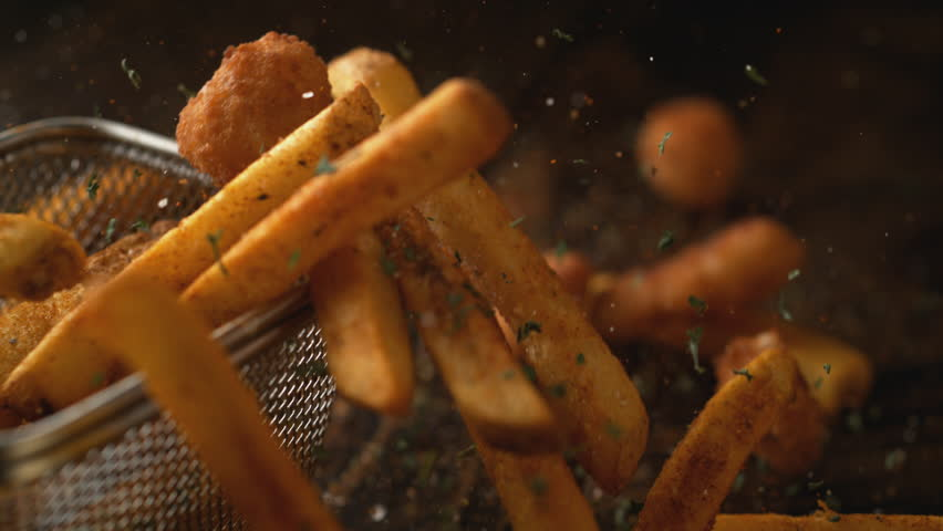 Camera follows french fries falling on wooden table. Shot with high speed camera, phantom flex 4K. Slow Motion.
